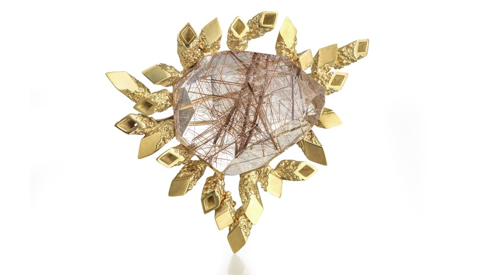 18ct yellow gold brooch of radiating textured square tubes, some closed off and polished – centre set irregular cut rutilated quartz. 1967