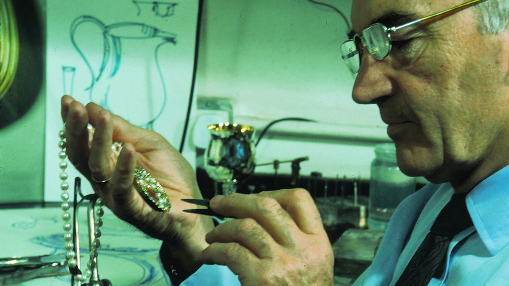 John Donald putting final touches to the bejewelled crown centrepiece of necklace. 1970