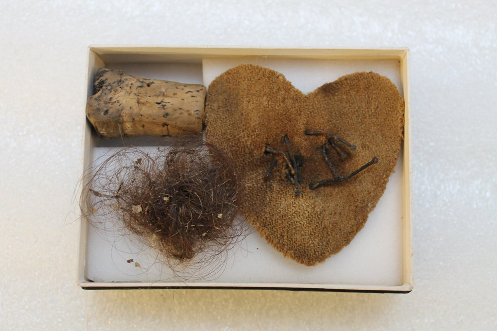 Cloth heart pierced with pins, human hair, nail parings and cork.