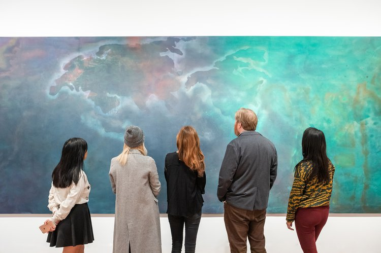 People look at a colourful abstract painting