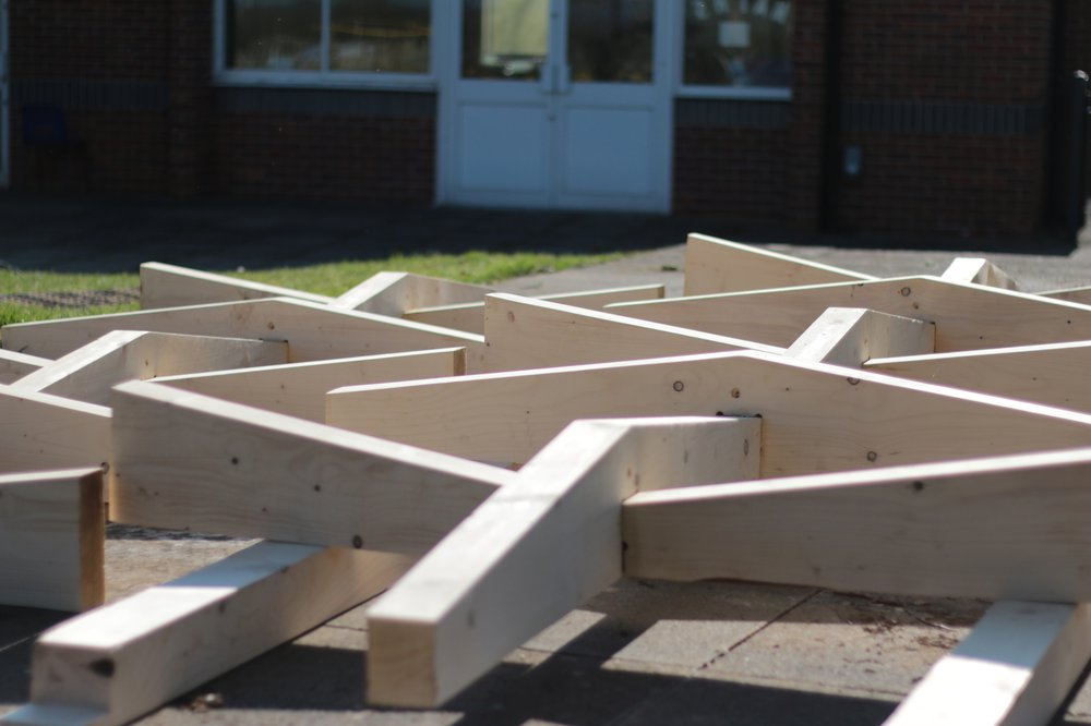 A partially assembled roof panel lying flat on the playground
