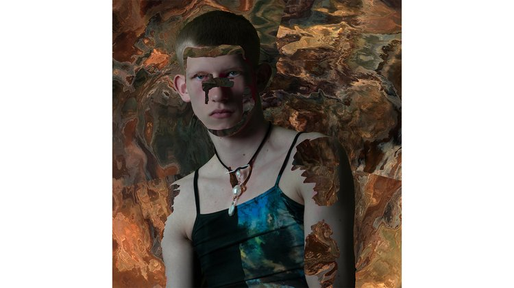 A male model with a shaved head wearing a blue-green dress and necklace in front of a bronze liquid backdrop