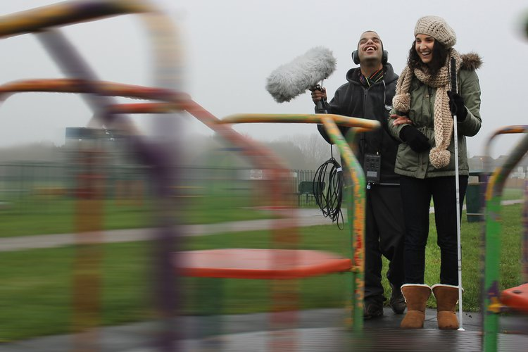 Two people with recording equipment near a roundabout