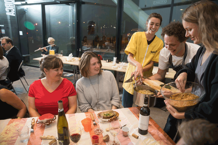 Two seated women are served pasta by three laughing young people
