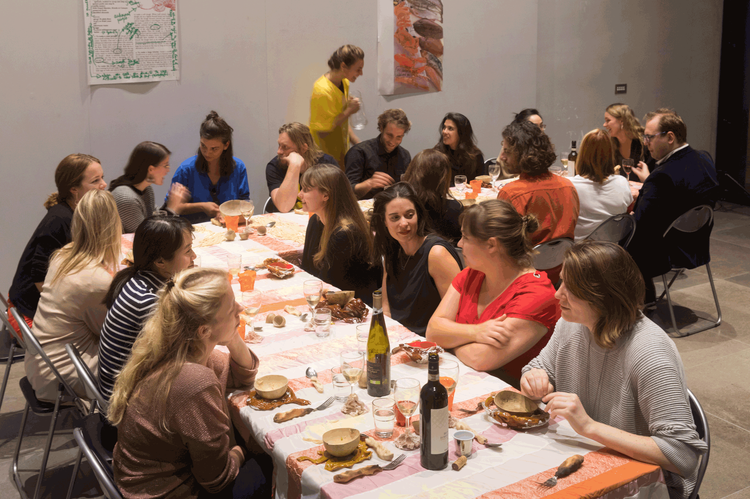 A group of people sit around a a dinner table in a gallery space