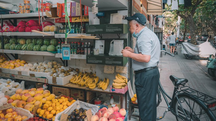 A man looks inside a fruit shop where there is an exhibition