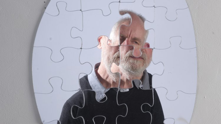 Photograph of David Johnson, reflected in a mirror, which is made up of jigsaw pieces