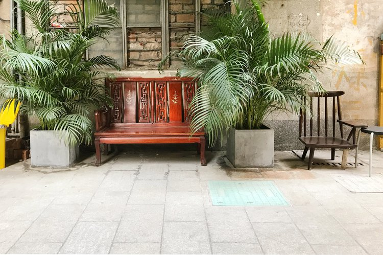 A mahogany sofa in a public space in Shenzhen. The materiality and almost a stage set up with the plants make it seems like a private living room in a public space. Am I allowed to sit on it?