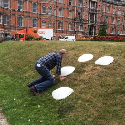 The artist David Johnson on his hands and knees installing the work 'Too Big to Feel' on a grassy slope