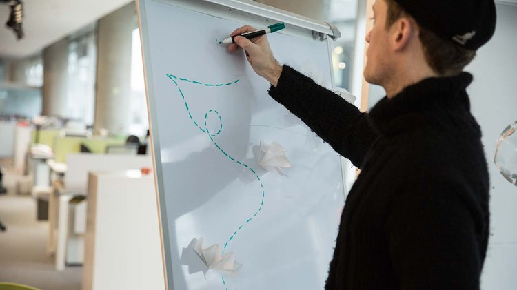 Design.Continuity Hero Image - person drawing on white board