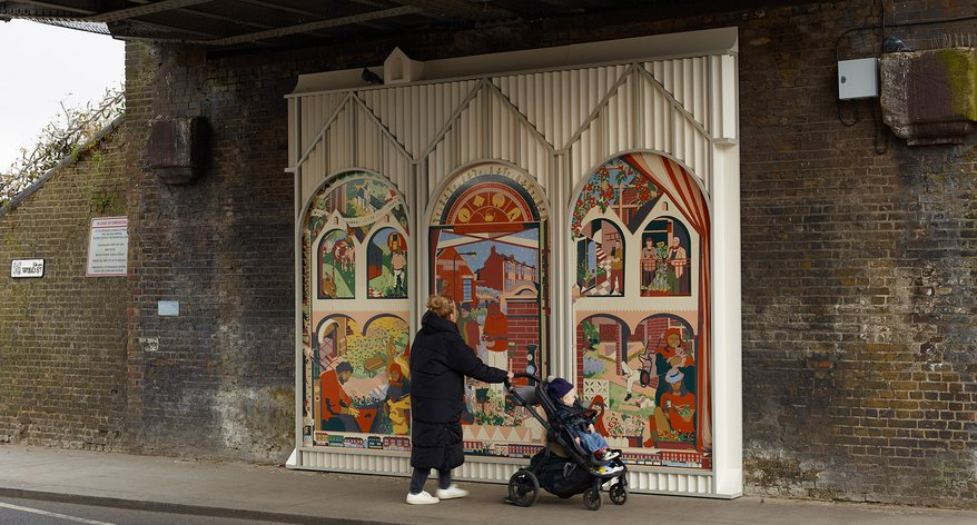 A woman with a baby in a pushchair looks at a mural underneath a railway bridge
