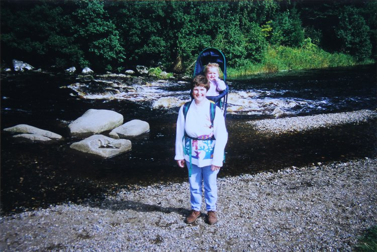 photograph of a woman with baby in a carrier next to a river