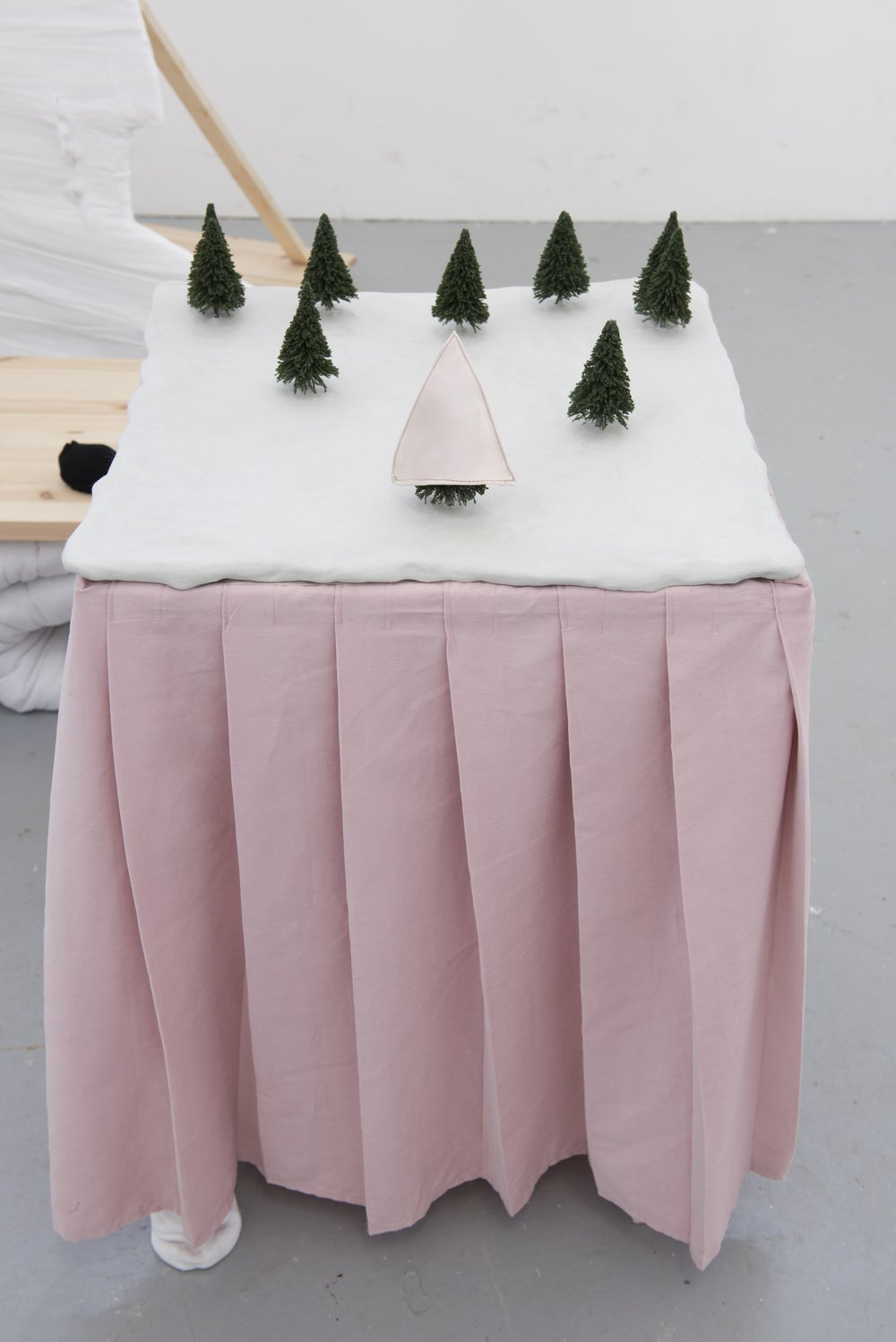 Complacent behaviour, Composition of trees on a table with a pink skirt