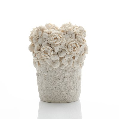 A porcelain sculpture featuring intricate daisy and feather sprigs