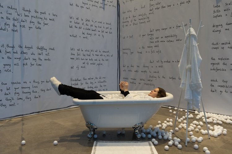 Women sits, dressed, in a bath filled with ping pong balls. The walls are covered in handwritten poetry.
