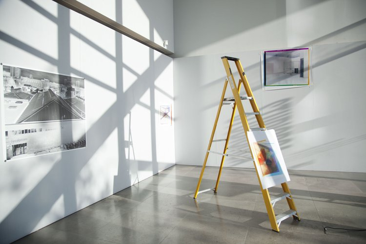 Installation view of an art exhibition, with a yellow ladder and unframed prints tacked to the wall