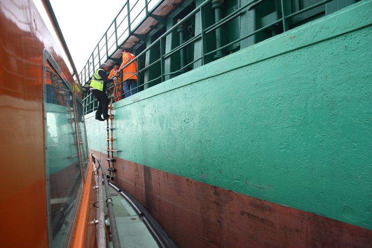 man climbs ladder onto a ship