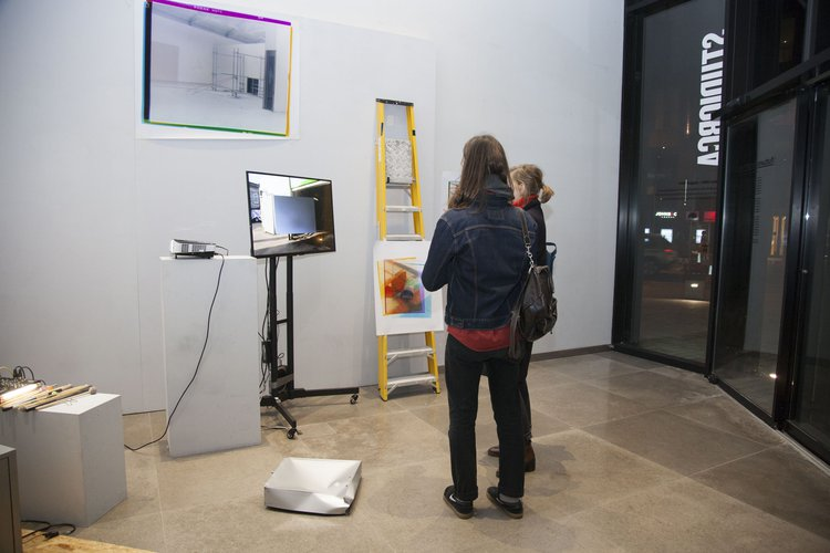 Installation view of an exhibition, with two women examining a screen on which is projected a loading bay.