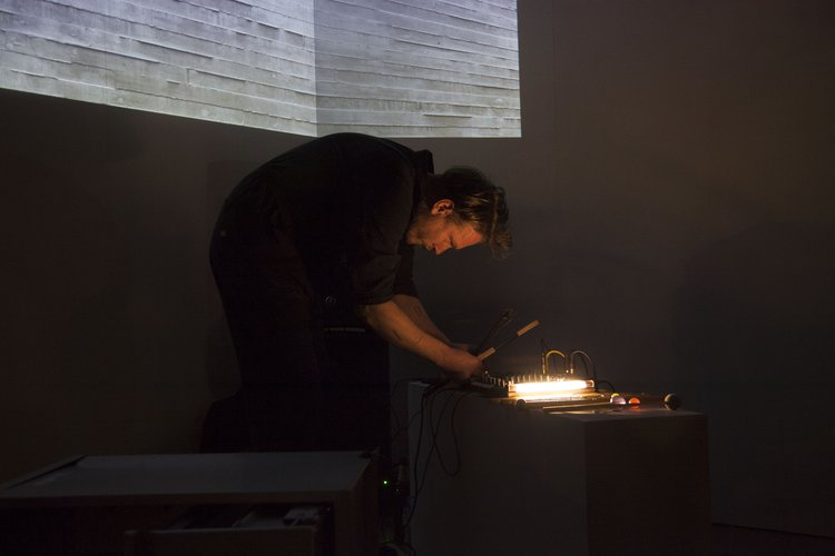 A person in a dark room bending over a sound interface, with an image of a concrete wall projected onto the wall behind them