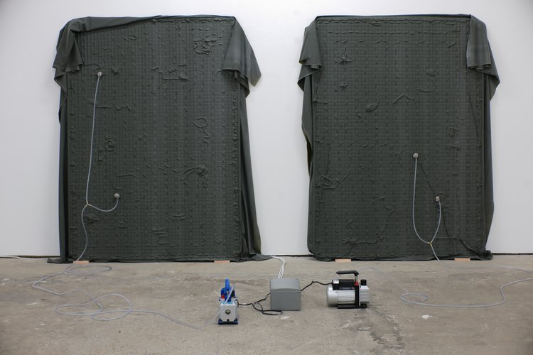 an installation view of an exhibition showing two dark grey sheets with plastic tubing attached to them, leaning against a white wall