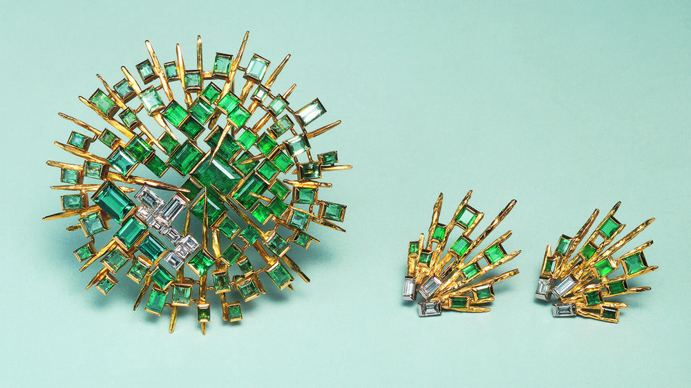 Concave brooch of 18ct yellow gold radiating rods with dark emerald set in the centre and the colour of the stones becoming paler towards the outer rim; baguette diamonds are offset. Shown with matching earrings. 1965