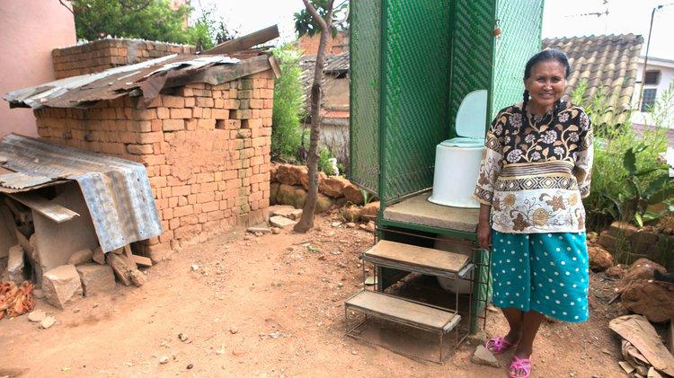 Women standing beside LooWatt toilet outside