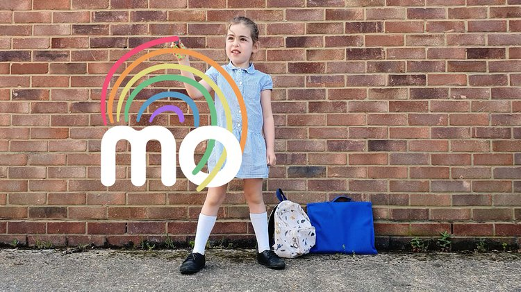 A school child against a brick wall draws a rainbow in the air, which is superimposed on the photograph above the word MO