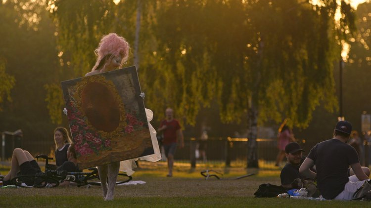 woman in pink wig carries a painting through a park