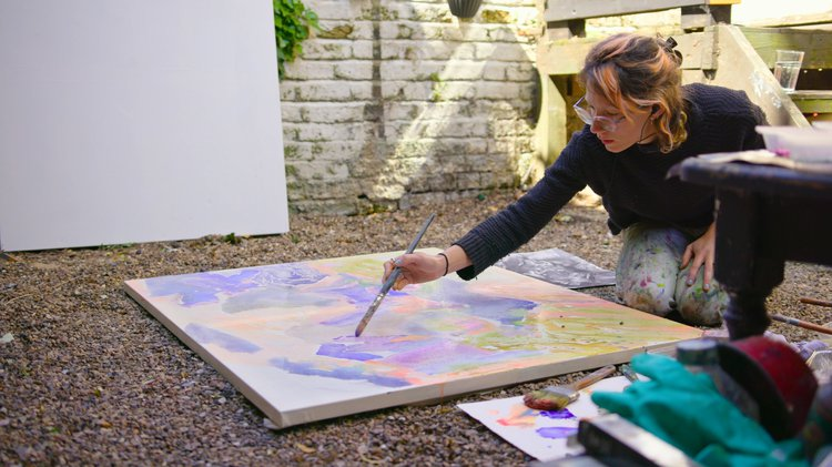 woman kneels to paint on a canvas