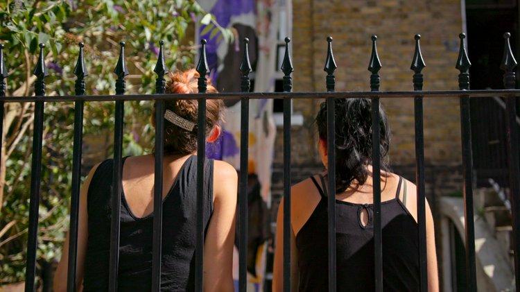 the backs of two women seen through metal railings