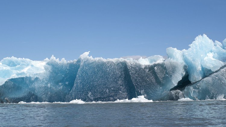 A photograph of an iceberg with blue sky above
