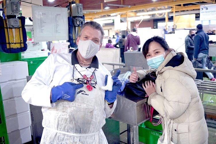 RCA student Pat Wingshan Wong poses with a fishmonger at Billingsgate fish market, both giving the camera a thumbs up