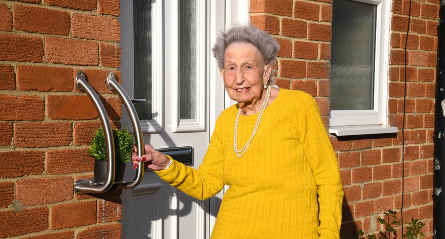 A photograph of Sheila Webster, the inspiration behind Invisible Creations®, alongside the company's Plant Pot Holder