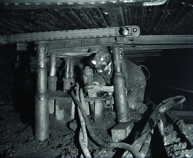 an a smiling image of a woman's face has been superimposed in an archival black and white photograph of a miner