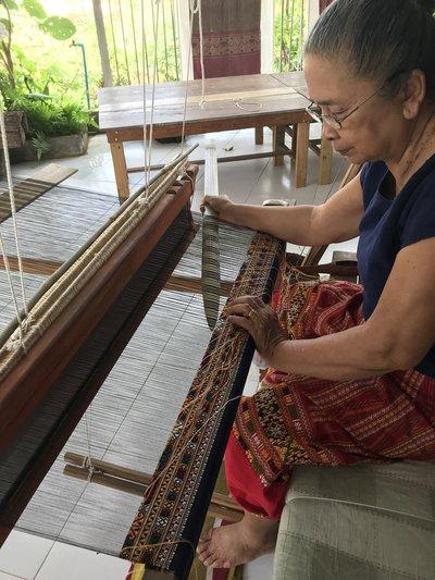 A Thai weaver sits at a loom
