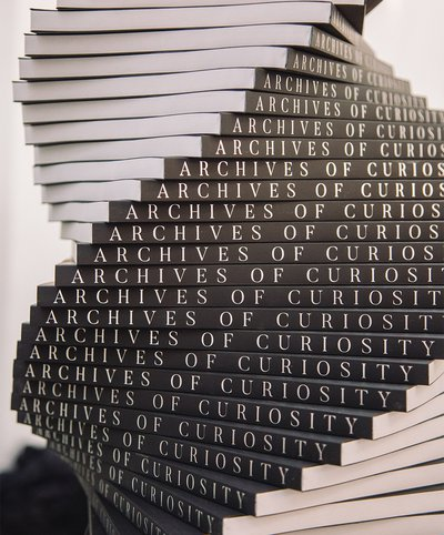 The black spines of books that say 'Archives of Curiosity' in white text